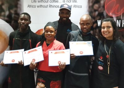 The Top Three Latte Art winners:  Karabo (3rd); Thandiwe (2nd) and the winner Mqondisi with Khulekani and Wise Coffee Holdings brand manager, Sandy Varty.